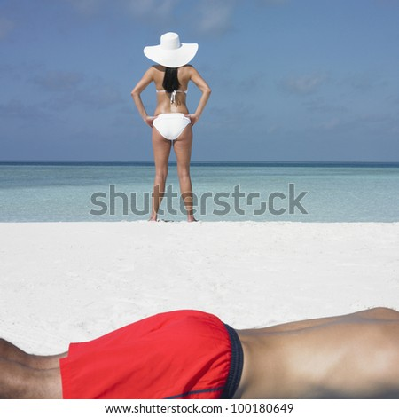 Young woman standing on the beach as boyfriend sunbathes - stock photo