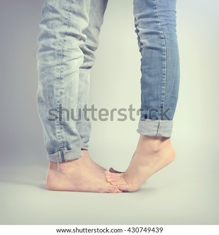 Young woman standing on the boyfriend's feet over grey background