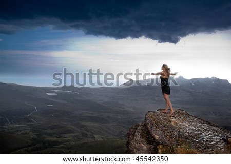 Young woman standing on the edge of a rock - stock photo