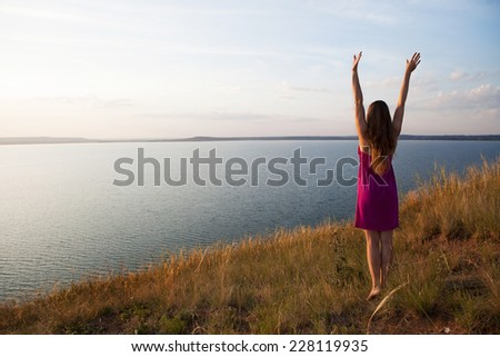 Young woman standing on the fild with her arms outstretched