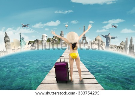 Young woman standing on the jetty while wearing swimwear and enjoy trip to the worldwide monuments - stock photo