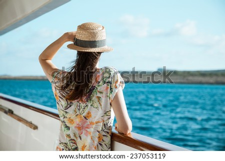 Young woman standing on the ship board and looking into the distance, rear view - stock photo