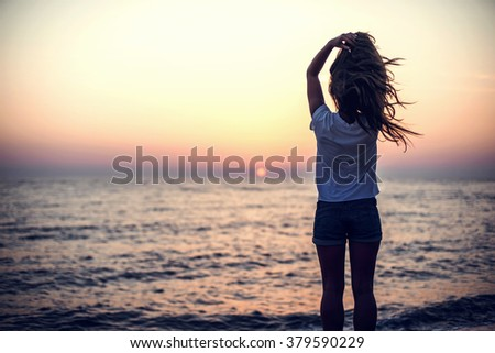 Young woman standing on the stone, looking at sunset over the sea - stock photo