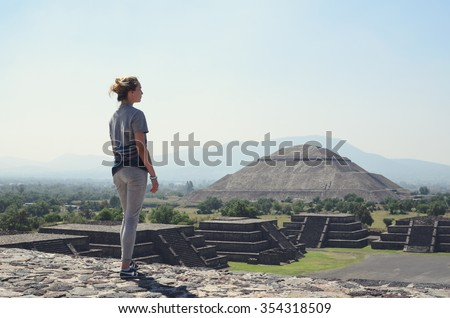 Young woman standing on top of pyramid and overlooking Teotihuacan - stock photo