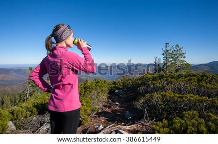 Young woman standing on top of the mountain enjoying warm sunny day and looking on mountain valley below. Tourist wearing pink jacket drinking tea out of thermos. - stock photo