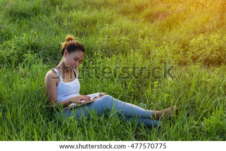 young woman standing reading book at meadows.
