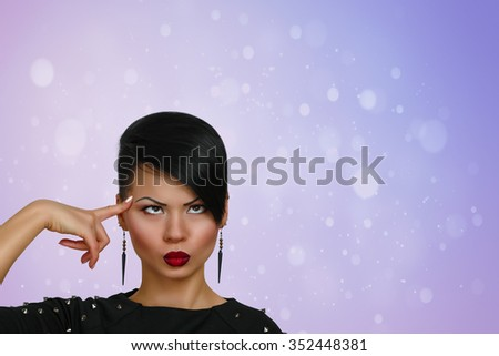 Young woman standing thinking with her finger raised and a grimace of concentration in a humorous stereotypical depiction, over a bokeh  background.  - stock photo
