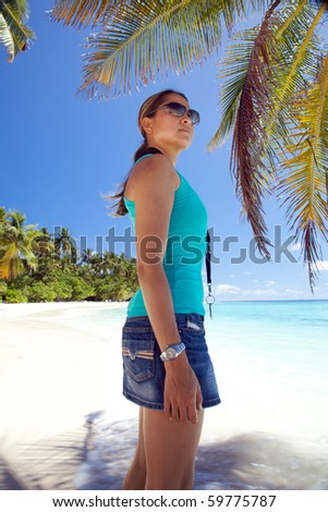 Young Woman Standing Under A Palm Tree On The Beach! - stock photo