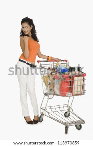 Young woman standing with a shopping cart and pointing - stock photo