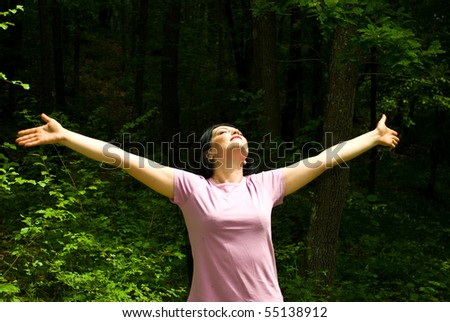 Young woman standing with arms open  and eyes closed to breath the clean air  from a spring forest - stock photo