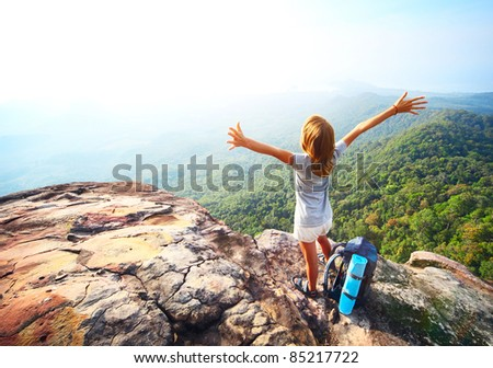 Young woman standing with backpack on cliff's edge and looking into a wide valley - stock photo