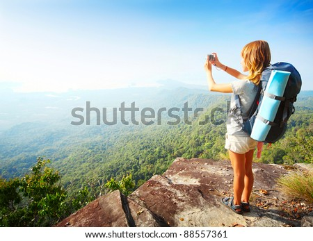 Young woman standing with backpack on cliff's edge and taking a photo of a wide valley