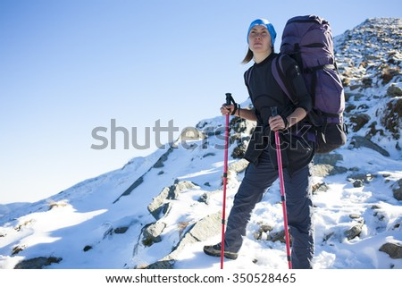Young woman standing with backpack on the background of mountains.