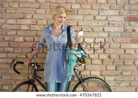 Young woman standing with bicycle, using mobile.