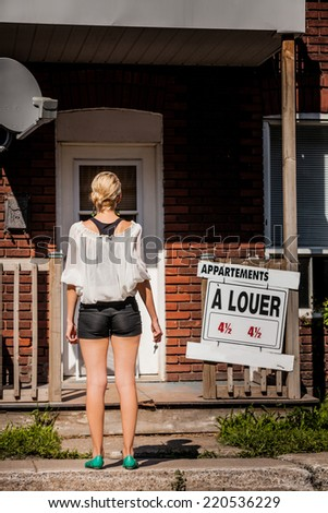 Young Woman standing with keys in front of her new apartment - stock photo