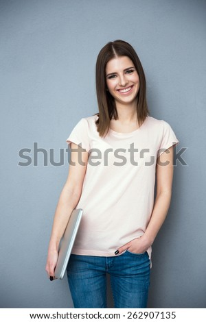 Young woman standing with laptop over gray background - stock photo