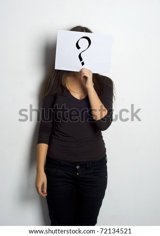 Young woman standing with question mark on board - stock photo