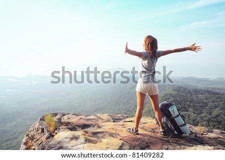 Young woman standing with raised hands with backpack on cliff's edge and looking into a wide valley - stock photo