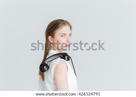 Young woman standing with retro phone tube on the shoulder and looking at camera isolated on a white background - stock photo