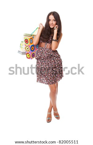 young woman standing with shopping bags on shoulder. studio shot. - stock photo