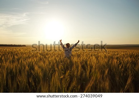 Young woman stands in a field of ripe wheat - stock photo