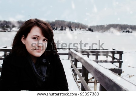 Young woman stands near a frozen lake. - stock photo