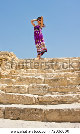 Young woman stands on the old stone steps