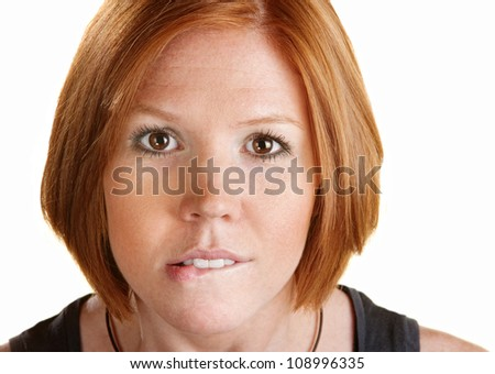 Young woman staring ahead and biting her lip - stock photo