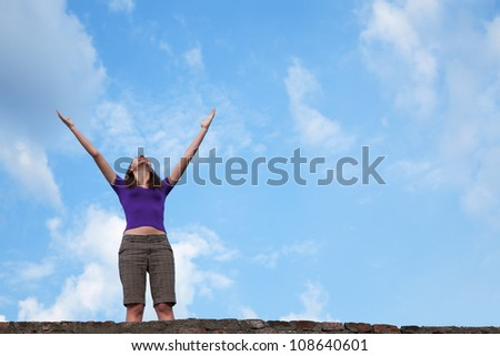 Young woman staying with raised hands against blue sky - stock photo