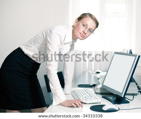 Young woman stays by computer and looks at camera