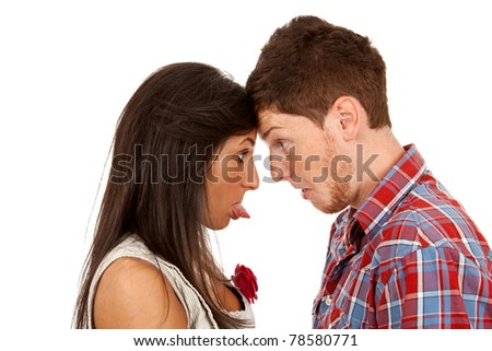 Young woman sticking out her tongue at a young man - stock photo