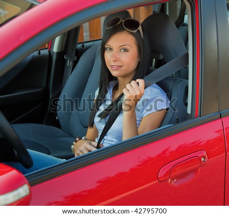 Young woman strapped to the seat belt in a car