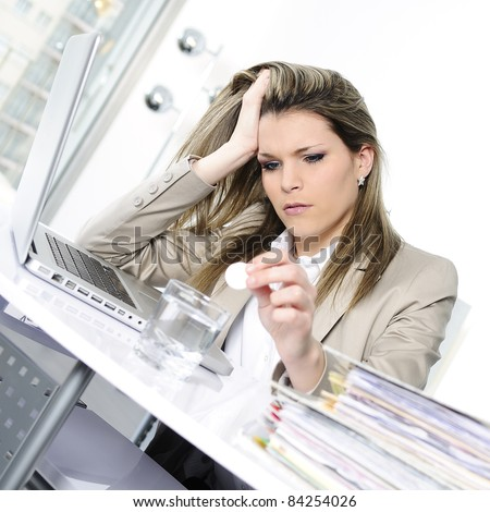 young woman stressed at work, taking an aspirin cahet - stock photo