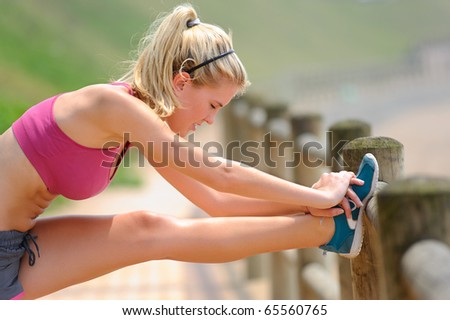 Young woman stretches along the pathway - stock photo
