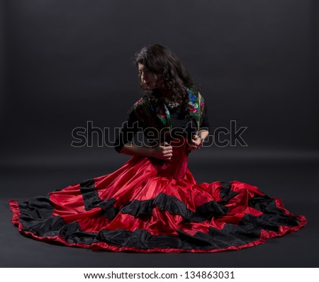 Young woman stretches back in spanish traditional clothes