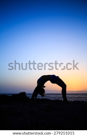 Young woman stretches yoga bridge pose, sunset silhouette in mountains. Motivation inspiration, sport and fitness stretching exercising outdoors in nature. - stock photo