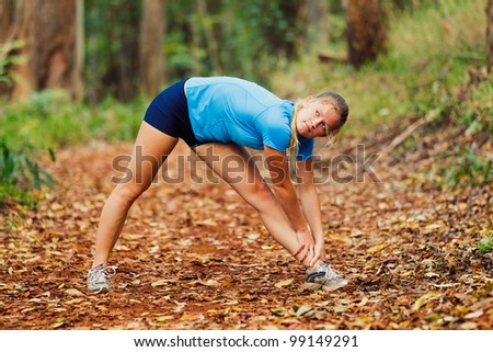 Young Woman Stretching after a Run in the Forest - stock photo