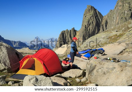 Young woman stretching at a campsite high in the mountains. - stock photo