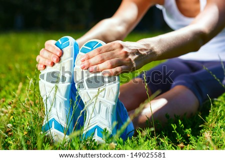 Young woman stretching before exercise - closeup shot.