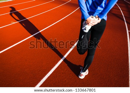 Young woman stretching before her run casts a shadow on the track - stock photo