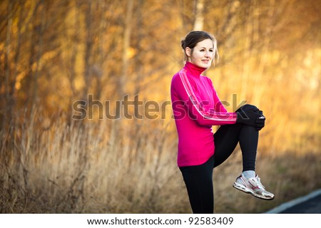 Young woman stretching before her run outdoors on a cold fall/winter day - stock photo