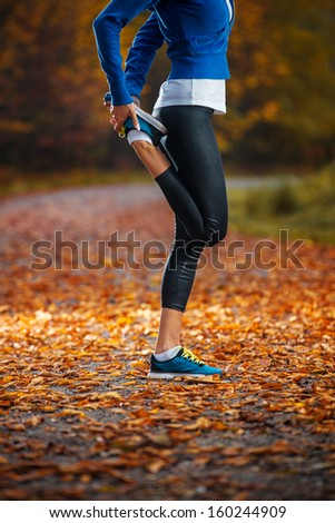 Young woman stretching before running in the early evening in the autumn