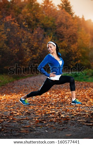 Young woman stretching before running in the early evening in the autumn - stock photo