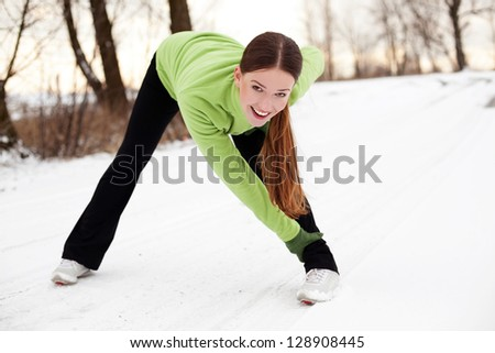 Young woman stretching before running in winter