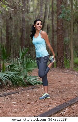 Young woman stretching before running in woods