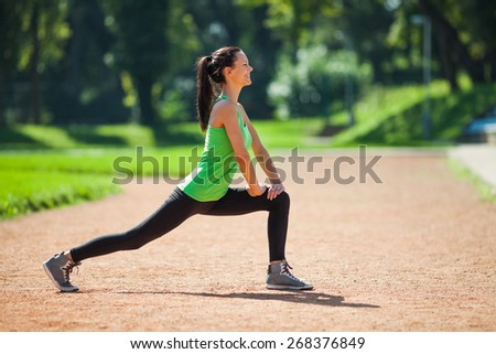 Young woman stretching body, warming up for jogging - stock photo