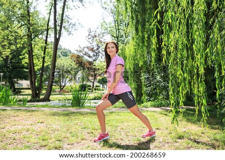 young woman stretching for running in a park or forest