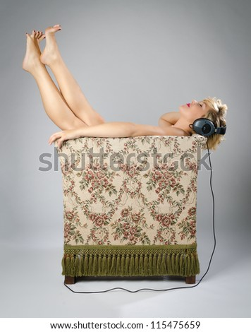 Young woman stretching her legs in an old chair while enjoying music on her headphones - stock photo