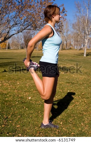 Young woman stretching her quad. - stock photo