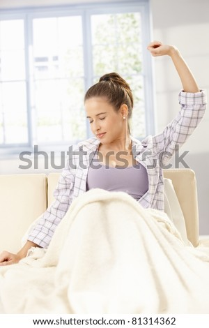 Young woman stretching in pyjama, sitting on sofa, smiling with closed eyes.? - stock photo